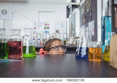 Elementary student looking at flasks while hiding behind desk in science laboratory