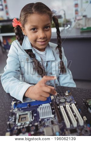 Portrait of elementary girl assembling circuit board on desk at electronics lab