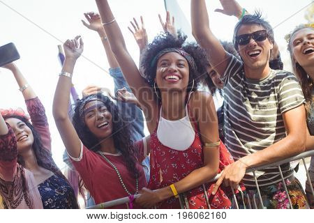 Cheerful friends by railing enjoying at music festival