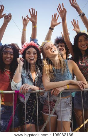 Happy female friends standing by railing while enjoying music festival