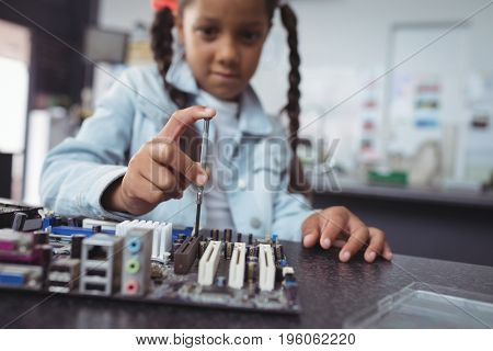 Elementary girl assembling circuit board on desk at electronics lab