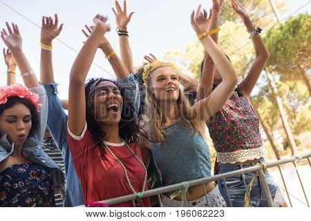 Cheerful female fans by railing enjoying at music festival