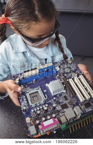 High angle view of concentrated elementary student examining circuit board on desk at electronics lab