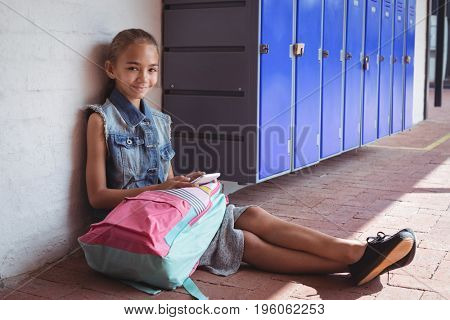 Portrait of elementary schoolgirl using mobile phone while sitting on pavement by lockers at school