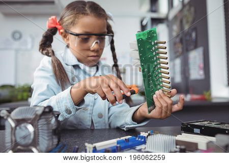 Concentrated elementary girl assembling circuit board on desk at electronics lab