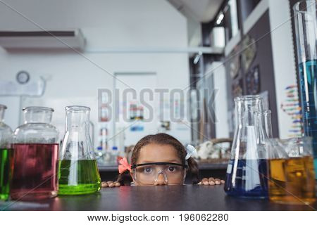 Portrait of elementary student hiding behind desk in science laboratory