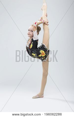 Young Caucasian Female Rhythmic Gymnast Athlete In Professional Competitive Suit Doing Vertical Split Exercise While Posing in Studio Against White. Vertical Image Orientation
