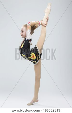 Young Caucasian Female Rhythmic Gymnast Athlete In Professional Competitive Suit Doing Vertical Split Exercise While Posing in Studio Against White. Vertical Image Composition