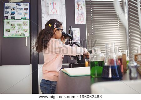 Side view of elementary schoolgirl using microscope on desk at science laboratory