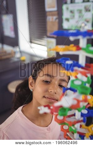 High angle view of elementary student looking at model in classroom