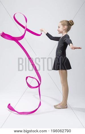 Portrait of Caucasian Female Rhythmic Gymnast In Professional Competitive Black Sparkling Starry Suit Doing Artistic Ribbon Spirals Exercises in Studio On White. Vertical Image