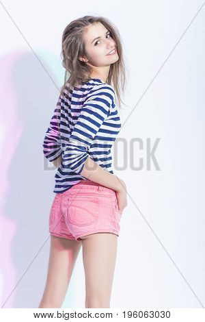 Youth Lifestyle Concepts and Ideas. Portrait of Caucasian Brunette Girl in Striped Shirt and Sexy Shorts. Standing Half Turned Backwards. Vertical Image
