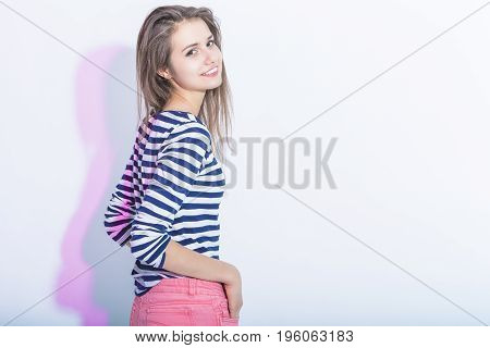 Portrait of Smiling Caucasian Brunette Girl in Striped Shirt and Pink Shorts. Standing Half Turned Backwards Against White. Horizontal Image Orientation