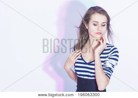 Portrait of Gentle and Sensual Caucasian Brunette Woman Posing Against White Background and Touching Face. Horizontal Image