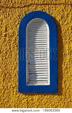 blue window on the yellow wall