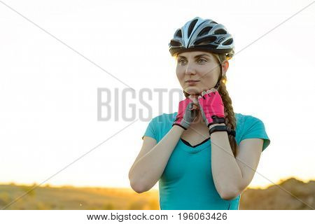 Young Woman Appareling Protective Bicycle Helmet near her Mountain Bike on the Summer Rocky Trail. Travel, Sports, Adventure and Safety Concept.