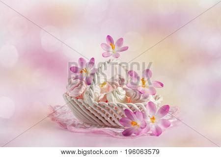 Delicate meringue in a dish with blooming crocuses