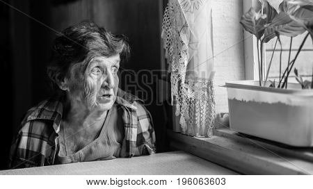 Elderly woman grieves near the window, genre photography in black and white.
