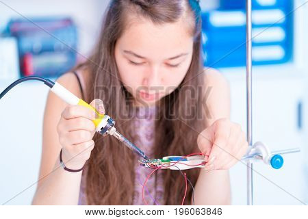 Schoolgirl in electronics class uses a soldering iron