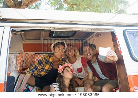 Happy young friends making faces while taking selfie in camper van