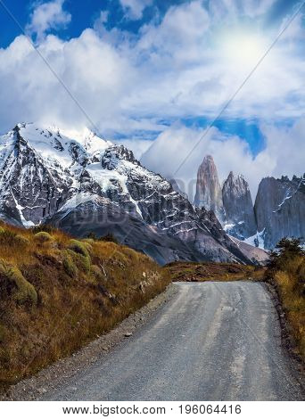 Legendary rocks Torres is surrounded by snow-capped black rocks. These leads dirt road. National Park Torres del Paine. Travel in Chile. The concept of active and extreme tourism