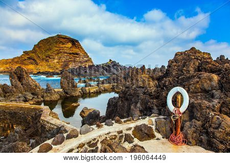 Volcanic island of Madeira. Small bay with smooth water. Rocks and grottoes of the Atlantic coast. The concept of exotic and ecological tourism