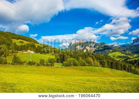 The concept of ecological tourism. Charming green grassy slope of the mountain. Rural pastoral in the Val de Funes, Dolomites. Warm autumn day