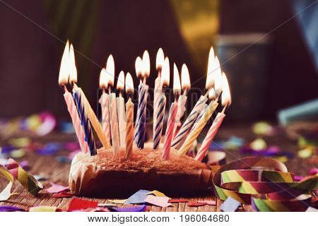 a small cake topped with some lit candles before blowing out the cake, on a rustic wooden table, sprinkled with confetti and a colorful garland in the background