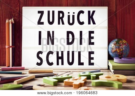 the text zuruck in die schule, back to school in german, in a lightbox placed against a rustic wooden background, surrounded by three-dimensional numbers and chalks and pencils of different colors