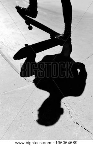 closeup of a young caucasian man skateboarding in an outdoors skate park, in black and white