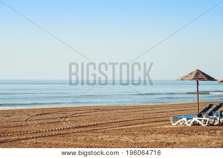 a view of a lonely beach in the mediterranean sea, with some sunloungers and a rustic umbrella made with natural fibers