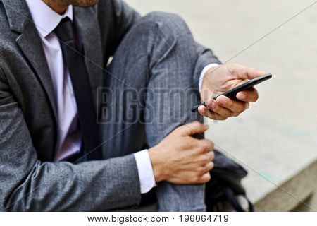 closeup of a young caucasian businessman in a gray suit using a smartphone outdoors