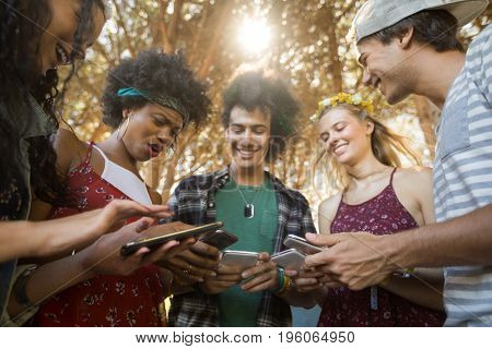 Happy friends using mobile phones together against trees at campsite