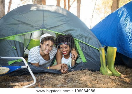 Portrait of couple with arm around relaxing in tent at campsite