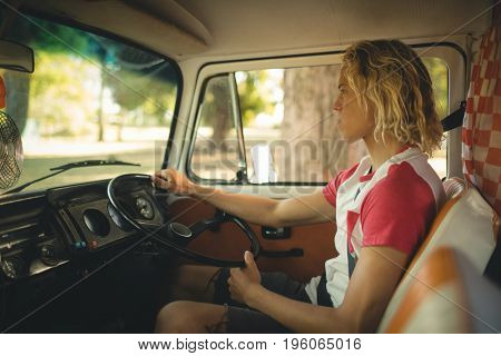 Side view of young man looking away while driving camper van