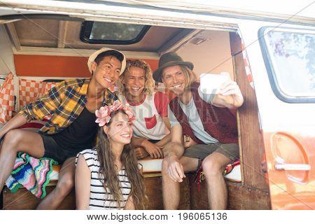 Happy young friends taking selfie while sitting in camper van