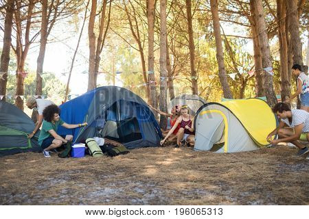Friends setting up tent at campsite on sunny day