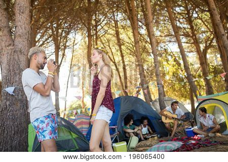 Side view of smiling man photographing girlfriend with friends in background at campsite