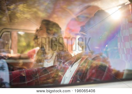 Cheerful friends in camper van seen through glass