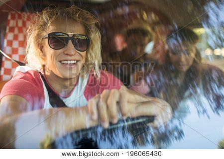 Smiling friends sitting in camper van seen through windshield
