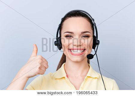 Successful Young Brunette Girl In Headset On A Pure Light Background, Wearing Casual Yellow Tshirt,