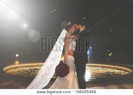 Groom and bride in romantic moment at night