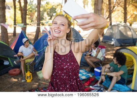 Happy woman gesturing while taking selfie at campsite