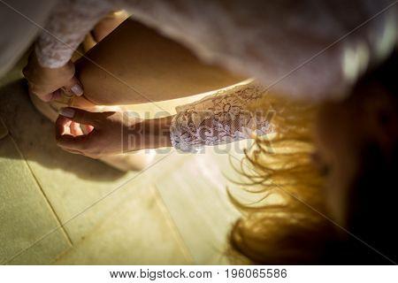 Ballerina tying her ballet slippers on