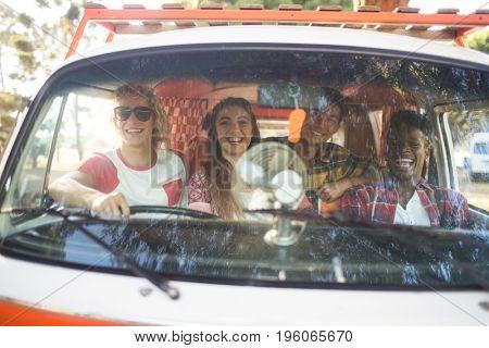 Portrait of cheerful friends sitting in camper van seen through windshield