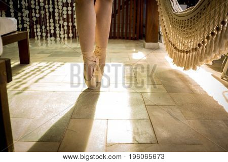 Young ballerina or dancer girl dancing, closeup on legs and shoes, standing in pointe position