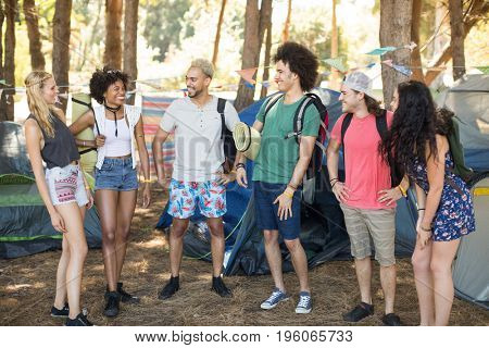 Smiling friends talking while standing by tents on field at campsite