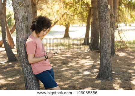 Side view of man using mobile phone while leaning on tree trunk at forest