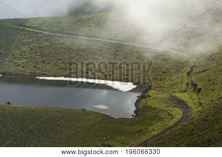 small lake among fog in a could morning at the island of Pico, in azores, Portugal