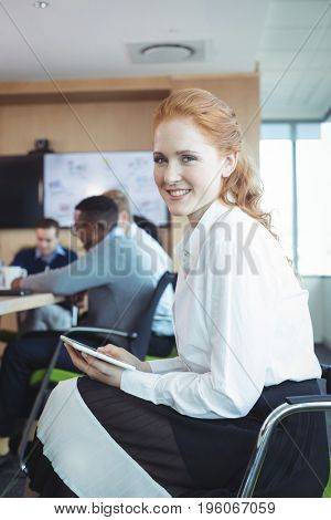 Portrait of businesswoman holding digital tablet while sitting on chair at office
